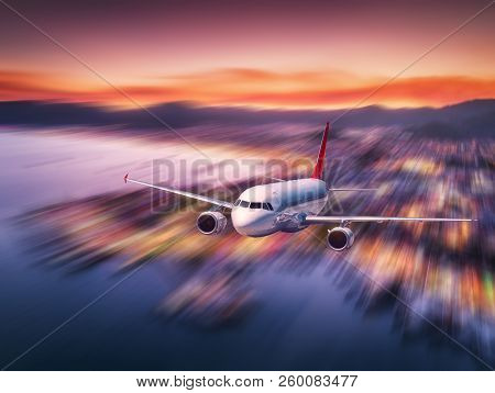 Airplane with motion blur effect is flying over sea coast at night. Landscape with passenger airplane, blurred buildings, city illumination, sea and sky. Aircraft. Business travel. Commercial plane stock photo