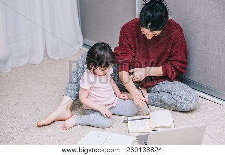 Business arhitect mother and her little curious daughter are working together on a floor at home and using a laptop and drawing something on the paper. Businesswoman working in the house with child. stock photo