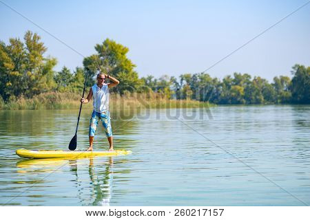 Sporty man paddling on a SUP board on large river smiling and enjoying life. Stand up paddle boarding - awesome active outdoor recreation. stock photo