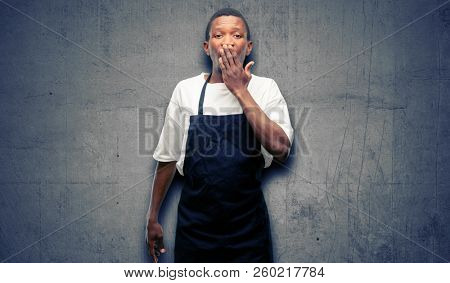 African man shop owner wearing apron covers mouth in shock, looks shy, expressing silence and mistake concepts, scared stock photo
