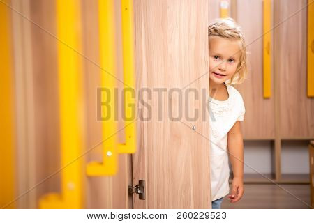 cheerful adorable kid standing in kindergarten cloakroom and looking out from locker stock photo