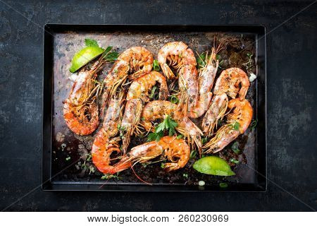 Traditional fried black tiger prawn with lemon as top view on a rustic old board  stock photo