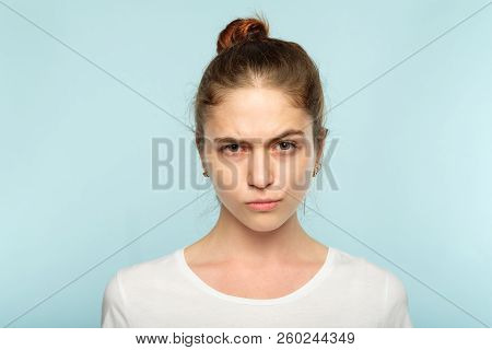 emotion face. frowning grumpy woman with pursed lips and piercing glance. young beautiful brown haired girl portrait on blue background. stock photo