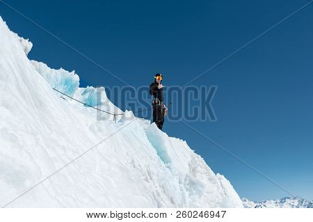A mountaineer stands on the edge of a glacier with a snow shovel in his hands and shows Shak's gesture against the blue sky. stock photo