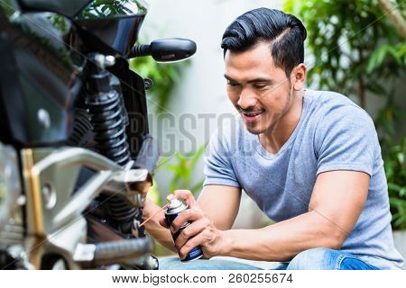 Lubricating motorcycle chain with dedicated chain spray grease stock photo