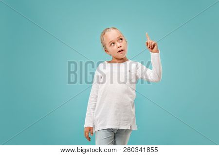 Remember all. Let me think. Doubt concept. Doubtful, thoughtful teen girl remembering something. Young emotional child. Human emotions, facial expression concept. Studio. Isolated on trendy blue. Front stock photo