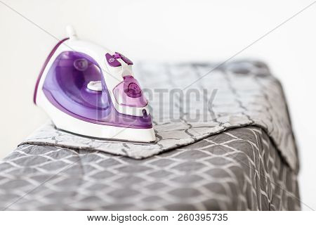Iron on ironing board on light home interior background. Ironing bed linen stock photo
