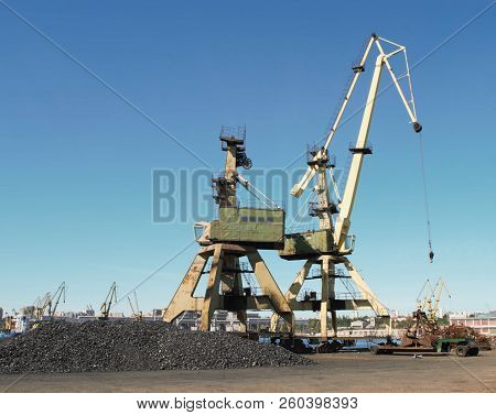 Cranes and charcoal in port with blue sky background - cargo / industry / transport / Constanta port stock photo