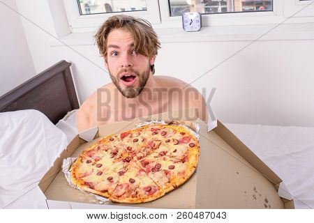Man Bearded Handsome Guy Eating Cheesy Food For Breakfast In Bed. Guy Holds Pizza Box Sit Bed In Bed