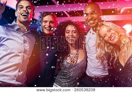 Happy young friends dancing together at party night with confetti. Group of beautiful women and eleg