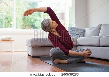 Senior woman exercising while sitting in lotus position. Active mature woman doing stretching exerci