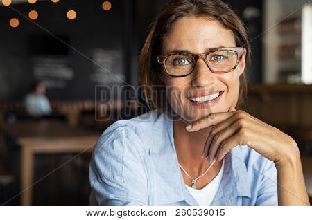 Portrait of happy mature woman wearing eyeglasses and looking at camera. Closeup face of smiling wom