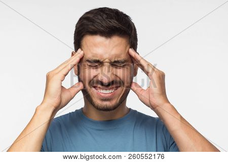 Portrait of young man isolated on grey background suffering from severe headache, pressing fingers to temples, closing eyes with helpless face expression stock photo
