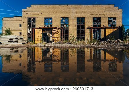 Abandoned industrial building reflected in pool of rainwater. stock photo