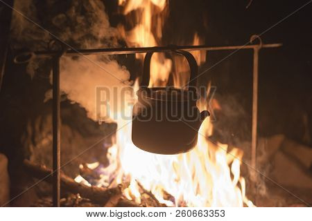 The kettle is heated on a fire at night outdoor stock photo