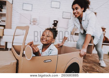 Mother and Young Girl Drive with Mother. People Play with Car. Little Girl Drive Car. Young People and Car. Relaxation with Mother. Car for Mother. Mother Push Car with Girl. Happt Time with Mom. stock photo