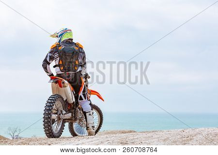 Motorcyclist in a protective suit sitting on motorbike in front of the sea stock photo