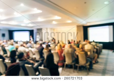 Blurred business seminar meeting with LED projector screen and speaker speech on stage. Defocused rear view audience in conference hall room, listening talk show in USA. Education, business concept stock photo