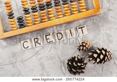 Word CREDIT laid out of handwritten letters on cardboard squares near old wooden abacus and three cones on gray cracked concrete stock photo