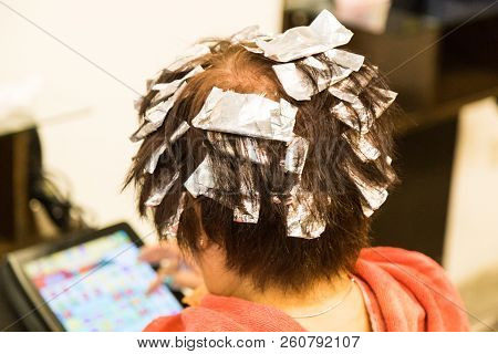 Closeup of hair dresser applying chemical color dye onto hair of customer in salon stock photo