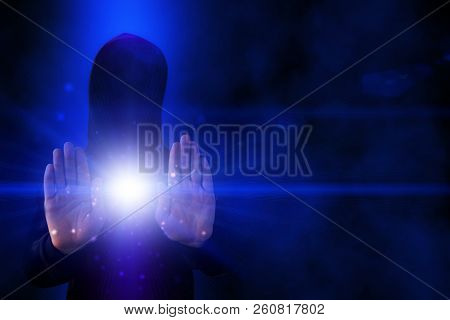 Abstract computer background with hacker in the hood. The flow of energy from the hands of a hacker. Decimal code, holograms, neon light stock photo