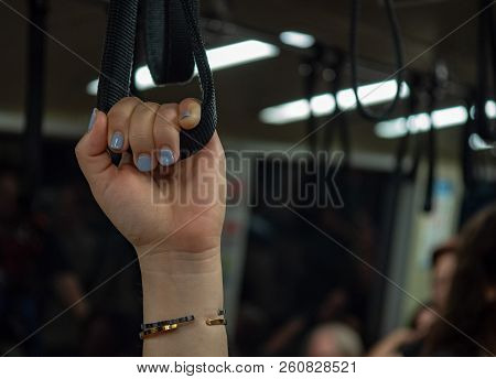 Womans manicured hand holding handrail handle on crowded subway training stock photo