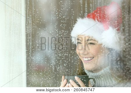 Happy woman looking through a window at home or hotel in chistmas rainy day stock photo