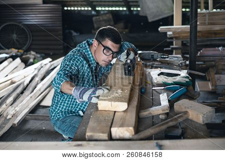Young man in plaid shirt, jeans, goggles and gloves planing wood manual planer in the workshop stock photo