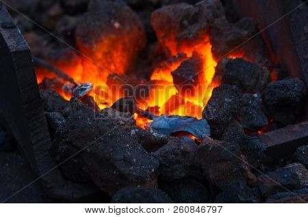 blacksmith furnace with burning coals, tools, and glowing hot metal workpieces stock photo