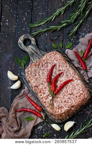 Raw ground meat with fresh herbs and pink Himalayan salt on a dark background stock photo