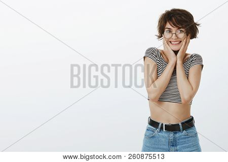 Canot hold my excitement inside. Portrait of cute joyful adult woman in round glasses and cropped top, smiling broadly and holding palm on cheeks, being pleased and overwhelmed with happiness stock photo