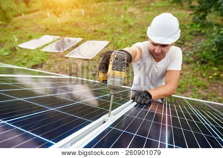 Smiling technician working with screwdriver connecting solar photo voltaic panel to exterior metal platform on sunny green orchard and rural houses background. Efficiency and professionalism concept. stock photo