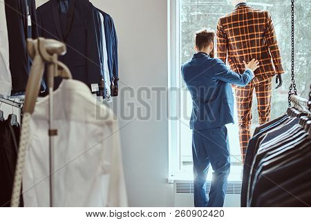 Stylish bearded seller care about suit on a mannequin in a menswear store. stock photo