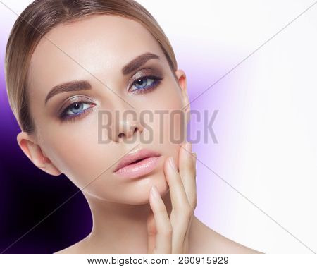 On a bright unusual background a portrait of the young woman, showing care of face skin. Fashionable make-up and chubby pink lips. Spa, cosmetology and beauty shop stock photo