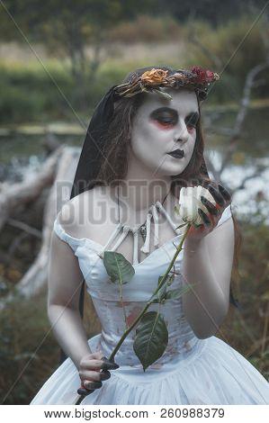 Creepy dead bride with white rose. Halloween scene stock photo