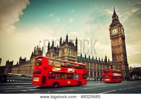 London, the UK. Red bus in motion and Big Ben, the Palace of Westminster. The icons of England in vi