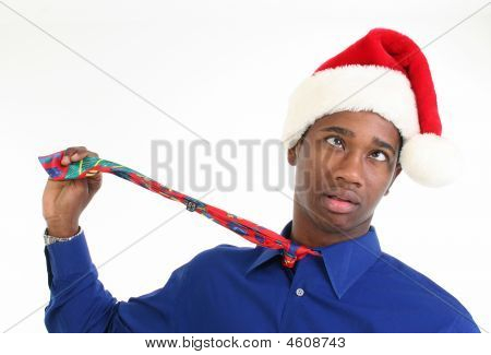 Worried or stressed African American man in santa hat choking himself with tie. stock photo