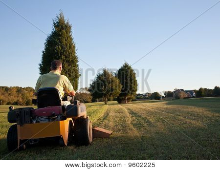 Middle aged man on zero turn mower cutting grass on a sunny day with the sun low in the sky stock photo