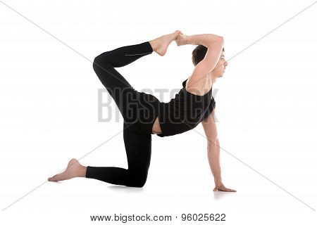 Sporty attractive young man working out doing Royal Sunbird exercise for abs and spine Chakravakasana balancing cat-caw variation (one side hand and leg) full length stock photo
