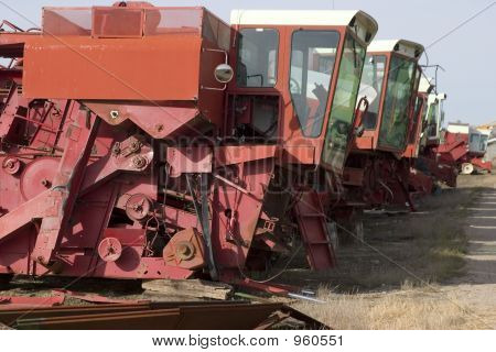 old combine harvester graveyard in a row stock photo