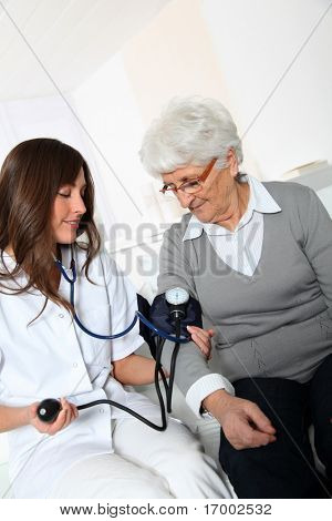 Closeup of nurse checking senior woman blood pressure stock photo