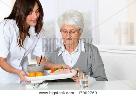 Beautiful nurse bringing meal tray to old woman at nursing home stock photo