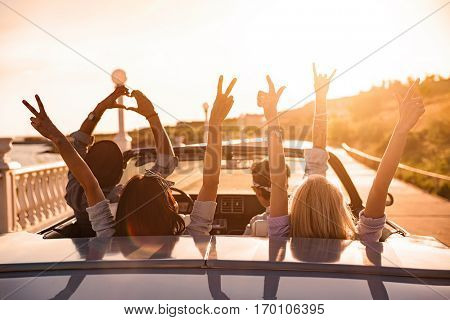 Group of happy young friends in cabriolet with raised hands driving on sunset