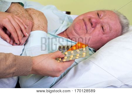 Picture of a sick elderly man with his carer holding medication stock photo