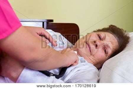 Picture of a sick elderly woman at home with her carer stock photo