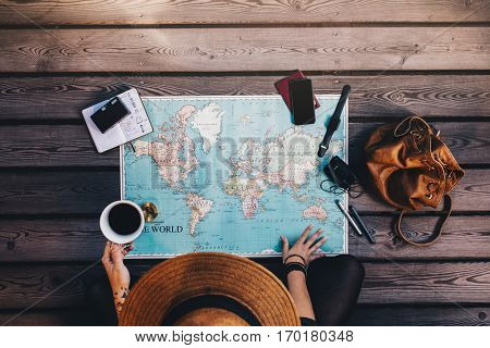 Young woman planning vacation using a world map compass and other travel accessories. Tourist looking at the world map holding a cup of coffee.