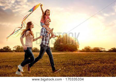 family running through field letting kite fly