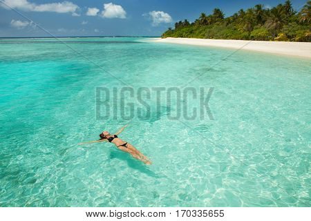 Woman swim and relax in the sea. Happy island lifestyle. White sand, crystal-blue sea of tropical be