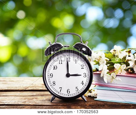 Alarm clock with books and spring blooming branch on wooden table against foliage background. Time c