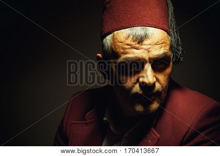 Traditional clothe style from Macedonia Bosnia or Serbia portrait of an adult man wearing red fez cap an jacket. stock photo